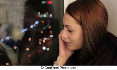 Girl sits on window sill and talking on phone - Young woman...