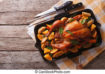 roasted chicken with apples and oranges in a pan. horizontal...