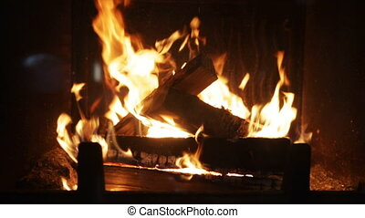 close up of firewood burning in fireplace - heating, warmth,...