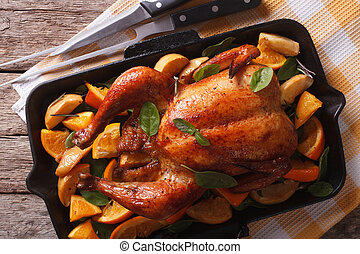 roasted chicken with oranges close-up in a pan. Horizontal...