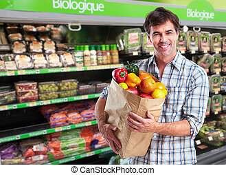 Man with grocery bag of vegetables.