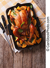 roasted chicken with apples and oranges in a pan. vertical...