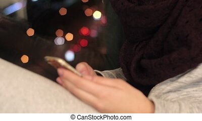 Girl sits on window sill and using smartphone - Young woman...