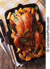 roasted chicken with oranges close-up in a pan. vertical top...