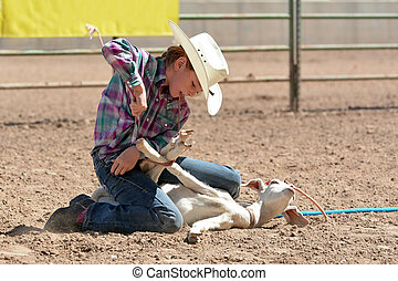Cowgirl Goat Tying - Young cowgirl tying the legs of a goat...