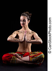 Mehendi. Pretty woman meditating in lotus position -...