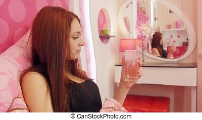 Ill woman in bed drink effervescent medicine - Young sick...