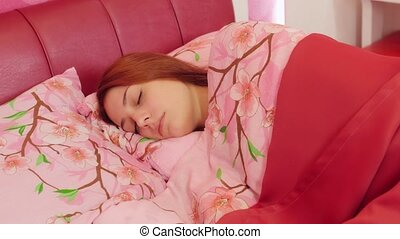 Woman sleeping in pink bed. Tossing and turning - Cute young...