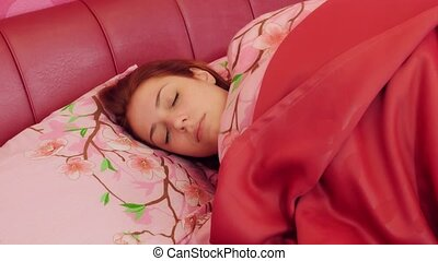 Woman in pink bed waking up and opening eyes - Young smiling...