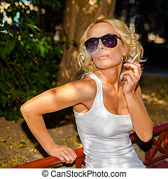 Close-up of sexy woman in sunglasses and white shirt smoking...