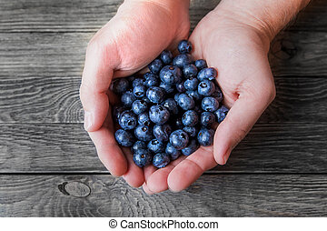 A man holds a handful of blueberries on wooden background. Rustic cozy background with healthy food. Fresh-gathered berries full of vitamins, good for diet nutrition and healthy meals.