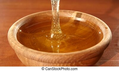 Taking honey by using spoon in wooden bowl, flowing down -...