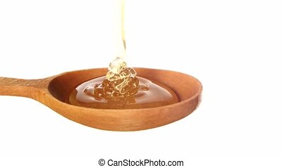 Honey dripping from a wooden honey dipper on white...
