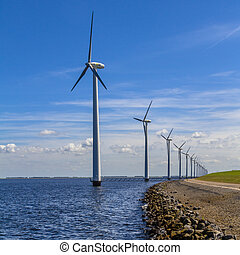 Row of Wind turbines along the shore
