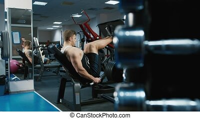 The athlete trains the muscles of the legs in a sports...