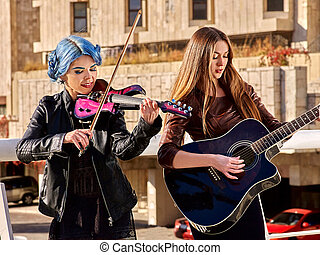 Woman playing violin and guitar. - Women performer playing...