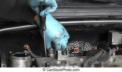 Removing fuel injector - Car mechanic wearing rubber gloves...