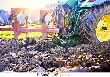 Old tractor ploughing soil in the agricultural field....