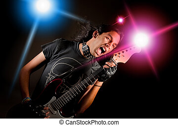 Rock star - Young handsome rock singer against a dark...