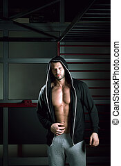 Man wearing hoodie posing in gym - Young adult man posing in...