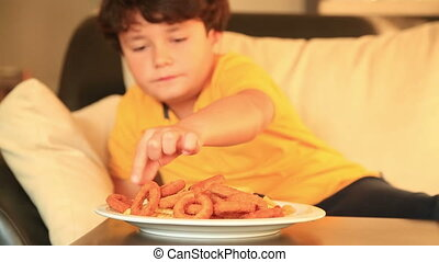 Eating onion rings and french fries - Young boy eating fried...