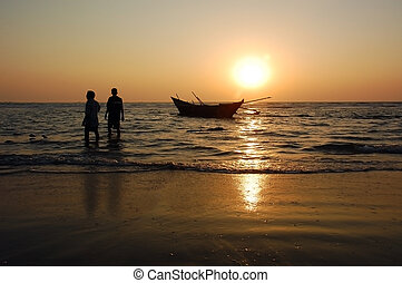 Fishermen at Sunset - Fishermen are walking away from the...