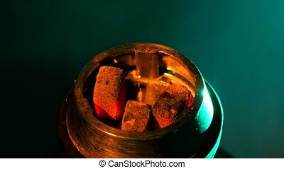 Coals on the bowl of shisha in the lounge cafe, close up -...