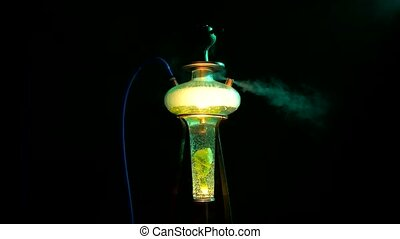 Colored yellow hookah with the smoke on black, close up -...
