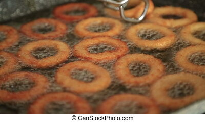 olden crispy onion rings frying in a pan