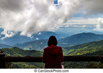 traveler woman standing looking view of mountain with cloudy...