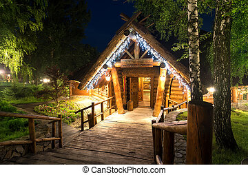 Wooden cottage in forest lit by lanterns at night