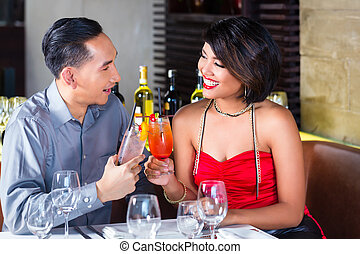 Asian couple drinking cocktails in fancy bar