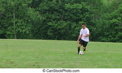 Soccer Player Dribbling - Soccer player dribbling ball,...