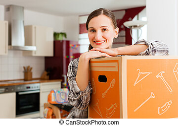 Woman with moving box in her house - Young woman with moving...