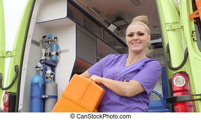 Emergency medical service female paramedic in front of...