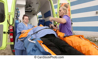 Emergency medical service paramedics female patient on...