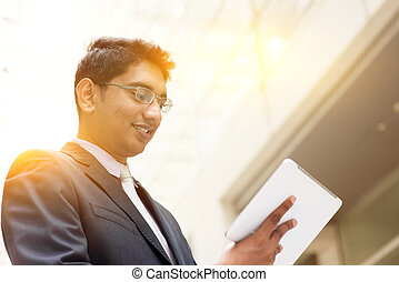 Asian Indian businessman using tablet computer - Portrait of...