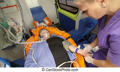 EMT paramedic preparing an intravenous infusion to patient...