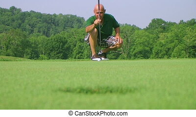 Golfer Sinks Putt 03 - Golfer sinks long putt, rack focus...