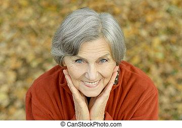 Happy elderly woman - Happy elderly woman enjoying in autumn...