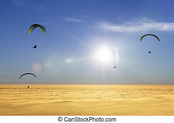 Four paragliders over a sea of clouds with sun