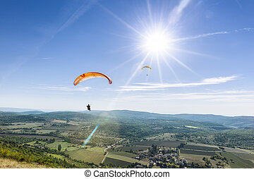 Two paragliders under the rays of a white sun