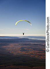 Yellow paragliding on plain with fall colors