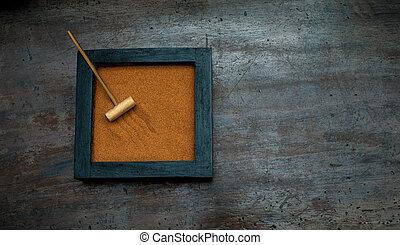 Zen garden with rake on orange sand