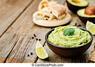avocado hummus on a dark wood background. toning. selective...