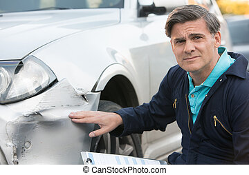 Auto Workshop Mechanic Inspecting Damage To Car And Filling...