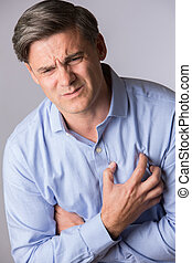 Studio Shot Of Mature Man Suffering Heart Attack