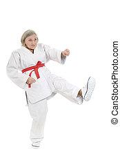 woman in karate pose - Senior woman in karate pose on white...