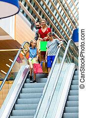 Family in shopping mall on escalators with bags