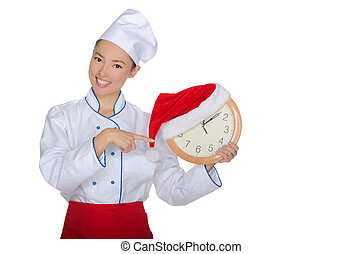 Asian chef points at clock with Christmas hat isolated in...